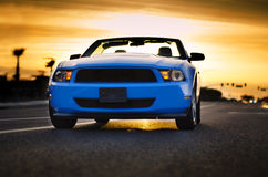 Convertible muscle car sunset background. On empty road Stock Photography