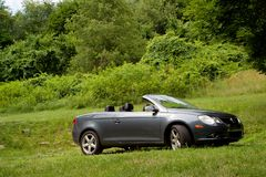 Convertible Parked in Field. A convertible car parked in a field of grass and trees Royalty Free Stock Photos