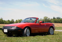 Convertible sports car. Red convertible Mazda Miata  parked in field Royalty Free Stock Photos