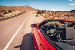 Convertible stopped on a shoulder in desert Royalty Free Stock Photos