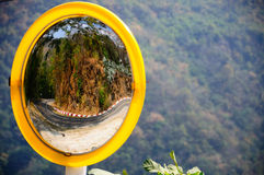 Convex mirror reflecting road curve on mountain Stock Images