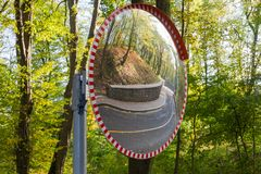Free Convex Spherical Traffic Mirror Mounted On A Winding Forest Road Stock Photo - 161658370