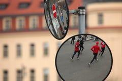 Convexe spiegels met de weerspiegeling van atleten het lopen stock foto