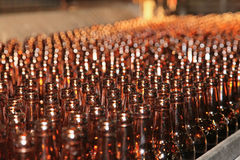 Conveyer line with many beer bottles. Conveyer line with many brown beer bottles in a plant workshop stock image