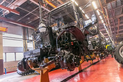 Conveyor assembly stage  the body of tractor at factory Stock Image