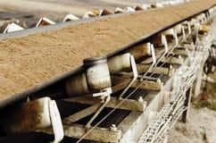 Conveyor belt. A conveyor belt loaded with sand Stock Image