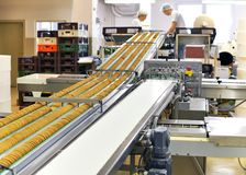 Conveyor belt with biscuits in a food factory - machinery equipm royalty free stock photos