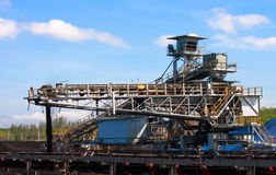 Conveyor belt carrying coal and emptying onto a huge pile. Royalty Free Stock Photography