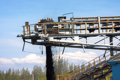 Conveyor belt carrying coal and emptying onto a huge pile. Stock Photography