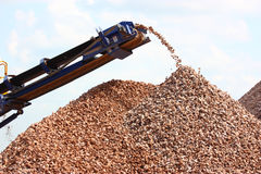 Conveyor belt on crusher. Conveyor belts that are part of a large stone crushing machine large with piles of gravel royalty free stock photo