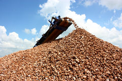 Conveyor belt on crusher. Making industrial gravel above large pile of gravel isolated on a cloudy sky background Stock Images