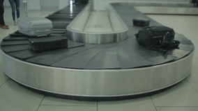 The conveyor belt moving with baggage in the airport. Close-up. The camera focuses on the luggage belt of the baggage claim desk at the airport. The luggage stock video footage