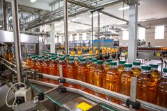Conveyor belt with organic juice in plastic bottles on beverage plant or factory. Close up stock images