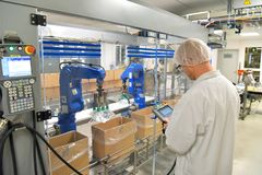 Conveyor belt worker operates a robot that transports insulin ba royalty free stock photo