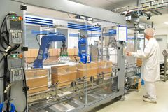 Conveyor belt worker operates a robot that transports insulin ba royalty free stock image