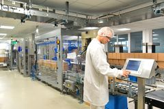 Conveyor belt worker operates a robot that transports insulin ba stock images
