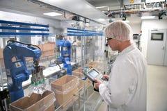 Conveyor belt worker operates a robot that transports insulin ba Stock Photos
