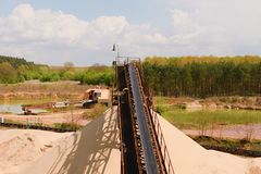 Conveyor belts and sand heaps. Construction industry. Sand quarry, heavy duty machinery. Horizontal  photo Stock Photos