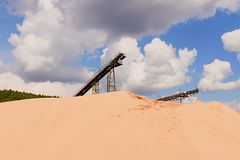 Conveyor belts and sand heaps. Construction industry. Sand quarry. Horizontal  photo Stock Photography