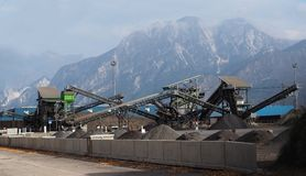 Conveyor belts with several piles of gravel in a plant under the Alps Stock Images
