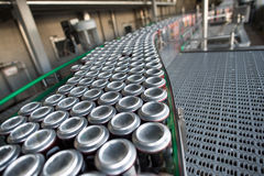 Conveyor with drinks in tin cans Royalty Free Stock Image