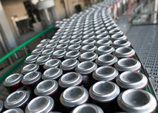 Conveyor with drinks in tin cans Royalty Free Stock Images