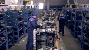 Conveyor with engines. Worker assembling motors, engines. view at factory workshop. View at factory conveyor with engines. Worker assembling motors, engines stock footage