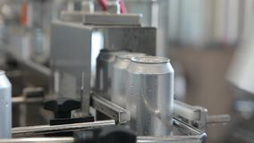 Conveyor for filling aluminum cans. Banks move along the conveyor and the person sorts them.