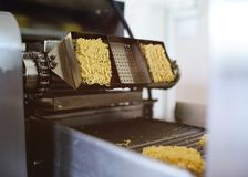 Production of instant noodles. Conveyor line for food production of instant noodles royalty free stock photos
