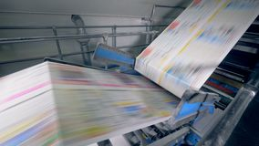A conveyor moving newspaper at printing office, close up. Typographical line works with newspaper