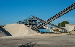 Conveyor over heaps of gravel on blue sky at an industrial cement plant. stock photos