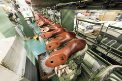 The conveyor of the shoe factory. The conveyor with shoe lasts. Shoe factory, mass production of footwear Stock Photo