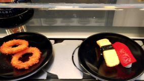 Conveyor sushi belt. Sushi tray on conveyor belt in restaurant stock footage