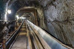 Conveyot della cinghia in tunnel sotterraneo illuminato immagini stock libere da diritti