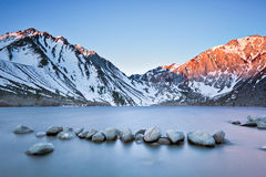 Convict of the Day. Some light snow and glowing storm clouds hanging on the Eastern Sierras behind Covnict Lake along the historic highway 395 in California Royalty Free Stock Image