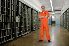 Convict, Prisoner, Criminal, Jailbird, Prison. A bank robber convict, prisoner, or jailbird. The male is a bad man or guy and is in prison by jail cells Royalty Free Stock Images