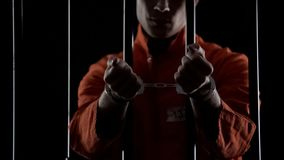 Convicted man showing handcuffs, standing behind prison bars, lawbreaking stock photo