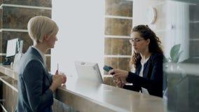 Convidado da mulher de negócios na conta pagando da recepção do hotel com o smartphone através da tecnologia sem contato do pagam video estoque