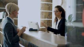 Convidado da mulher de negócios na conta pagando da recepção do hotel tecnologia sem contato do cartão de crédito do pagamento e  filme