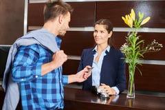 Convidado do hotel que paga com o cartão de crédito na recepção Fotos de Stock