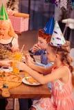 Convidados pequenos deleitados que apreciam o alimento festivo saboroso imagem de stock royalty free