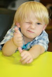 Convinced. Small boy at the desk in restaurant Royalty Free Stock Images