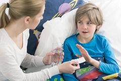Convincing the stubborn child to take medicine. Sick schoolboy in bed refusing to take the tablets his mother is giving to him Royalty Free Stock Photos