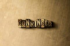 CONVINTO - il primo piano dell'annata grungy ha composto la parola sul contesto del metallo immagini stock