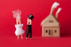 Convite do casamento e conceito do amor Caráteres do Peg do pregador de roupa do noivo da noiva, casa do cartão no fundo vermelho Fotografia de Stock Royalty Free