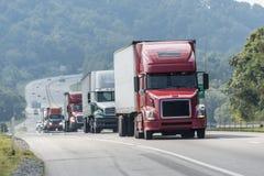 Convoglio di camion che viaggia sulla strada principale Immagini Stock Libere da Diritti