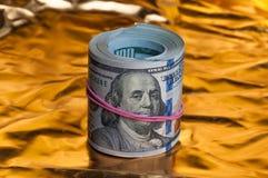 Convolving nota cem dólares em um fundo brilhante do ouro imagem de stock