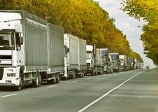 Convoy. Trucks caravan in scenery road Royalty Free Stock Image