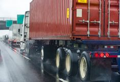Convoy of different big rig semi truck with commercial cargo in semi trailers and container running on the wet raining highway. Convoy of different big rigs semi royalty free stock photo