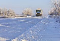 A convoy of heavy trucks drives along a snowy white road royalty free stock photo